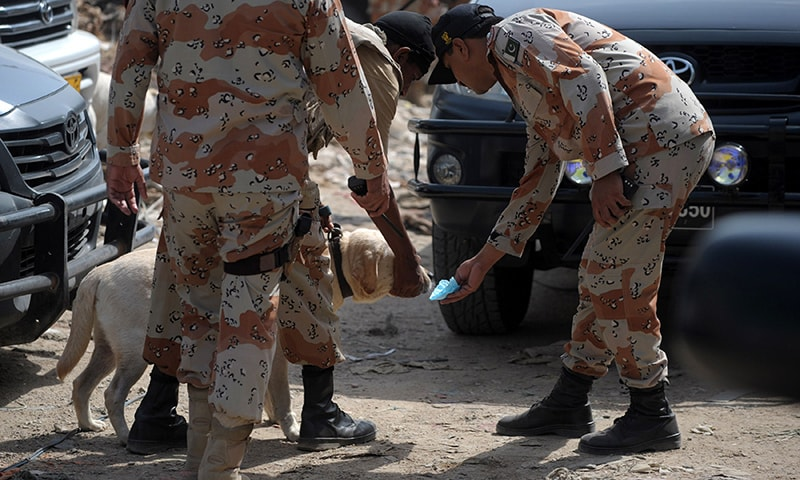 Security personnel collect evidence with the help of a dog after an attack on police vehicles in Karachi on May 27, 2015. — AFP