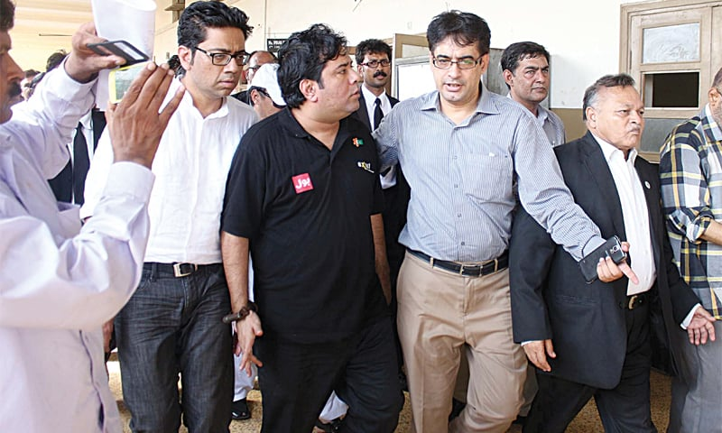 KARACHI: Axact CEO Shoaib Shaikh, escorted by FIA officials, is being taken to District South's Special Court here on Wednesday.—PPI