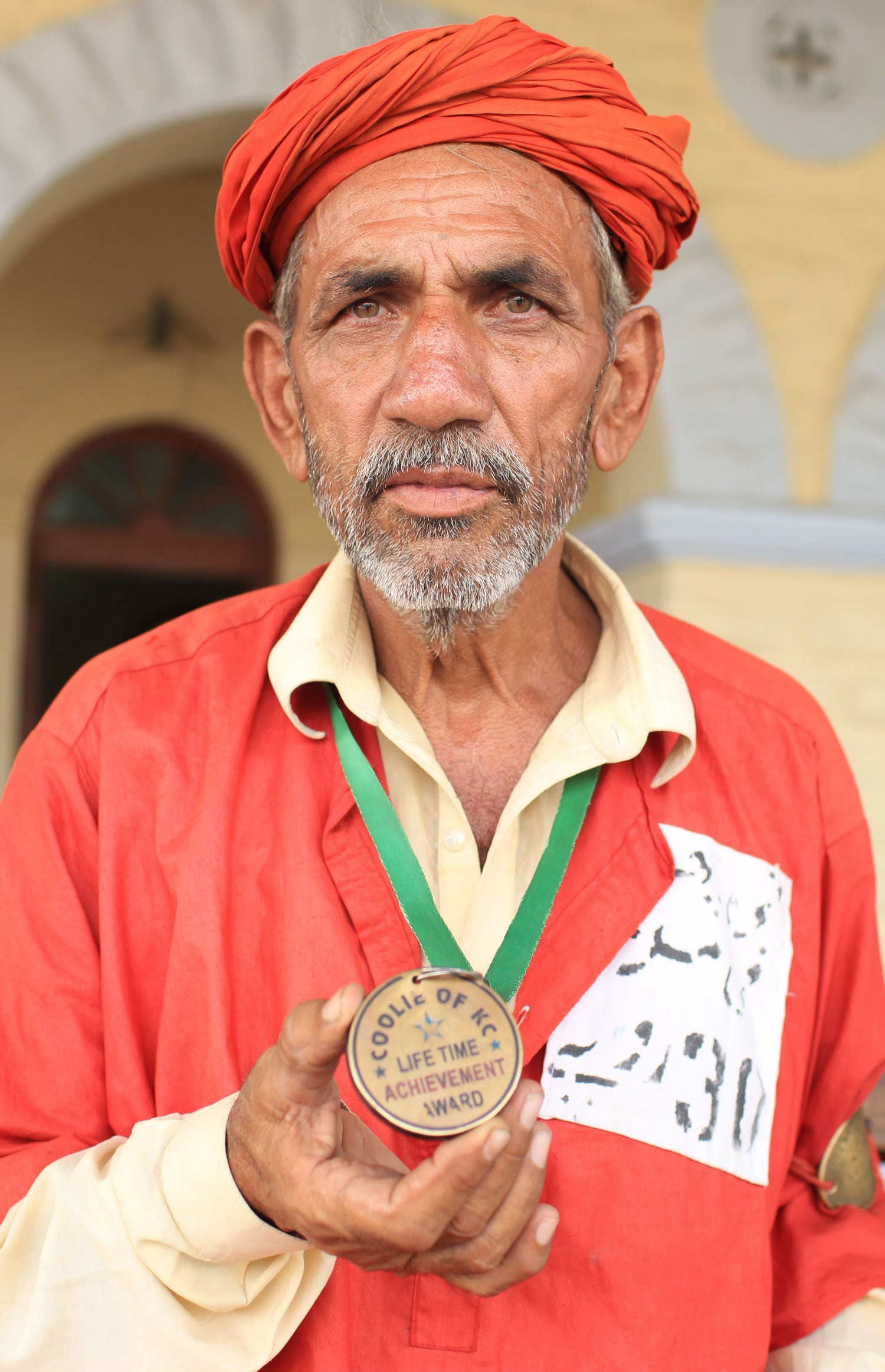 Khanzada shows the medal given to him by the Railway Minister Saad Rafique for being the oldest porter.
