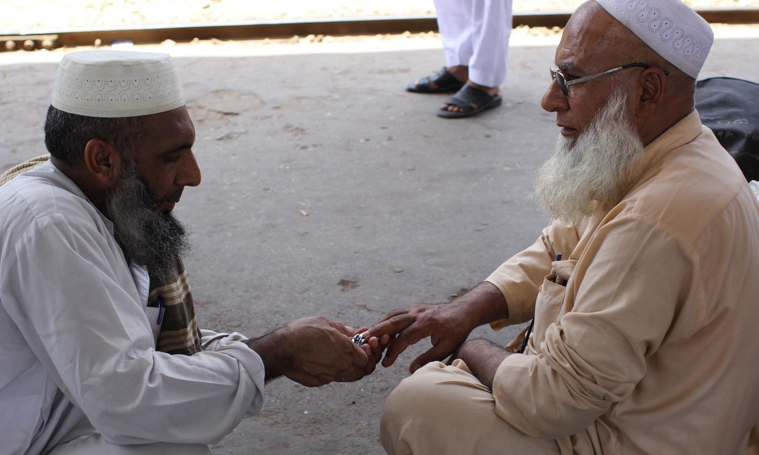 A man cutting nails of his relative.