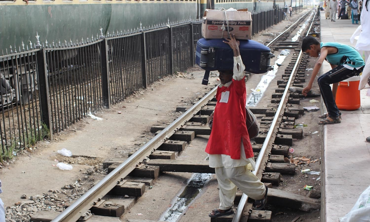 A porter with heavy luggage walks through the track.