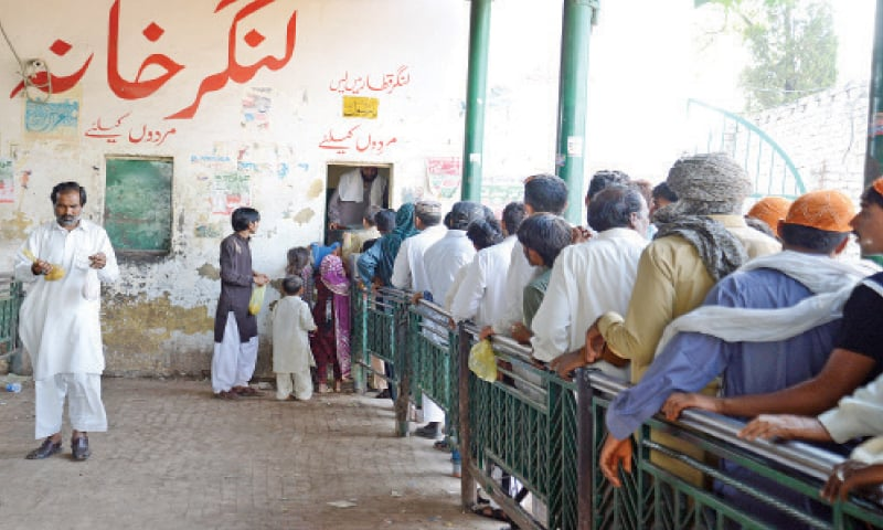 People queue outside the Langar Khana to get free food. In the other picture, people light earthen lamps at the shrine.