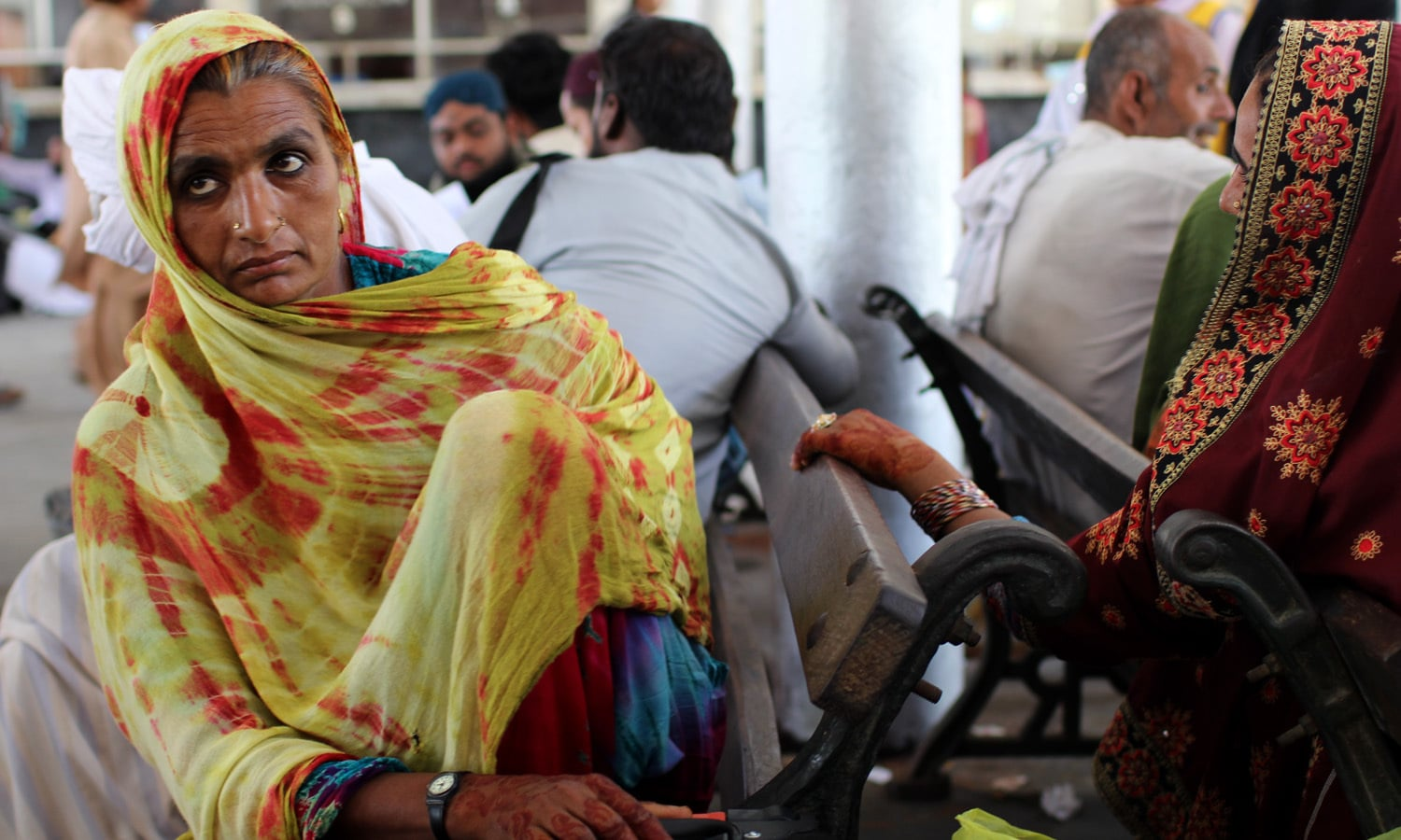A woman awaits her husband who is in a ticket queue.