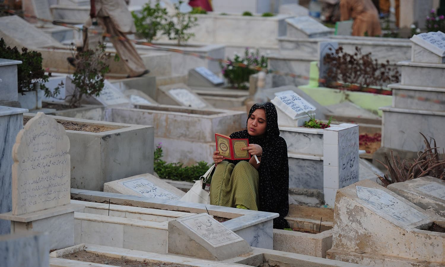 A Pakistani Muslim recites from the Quran beside the graves of relatives to mark Shab-e-Barat. ─ AFP