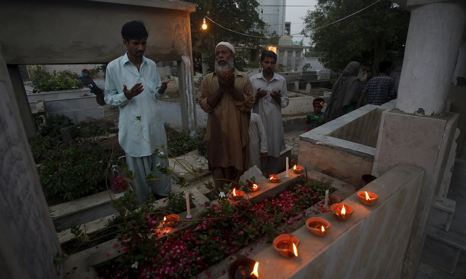 Men pray over the grave of their family member while observing the Shab-e-Barat festival at a cemetery. ─ Reuters