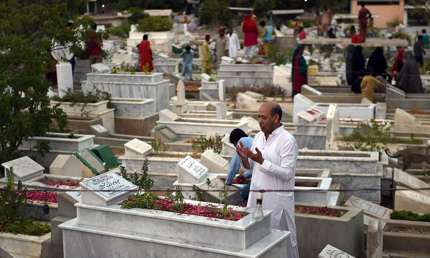 Pakistani Muslim families pray beside the graves of their relatives to mark Shab-e-Barat. ─ AFP