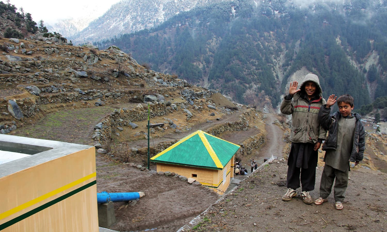 Two young locals wave into the camera at Kundi Mar Kalam in Swat
