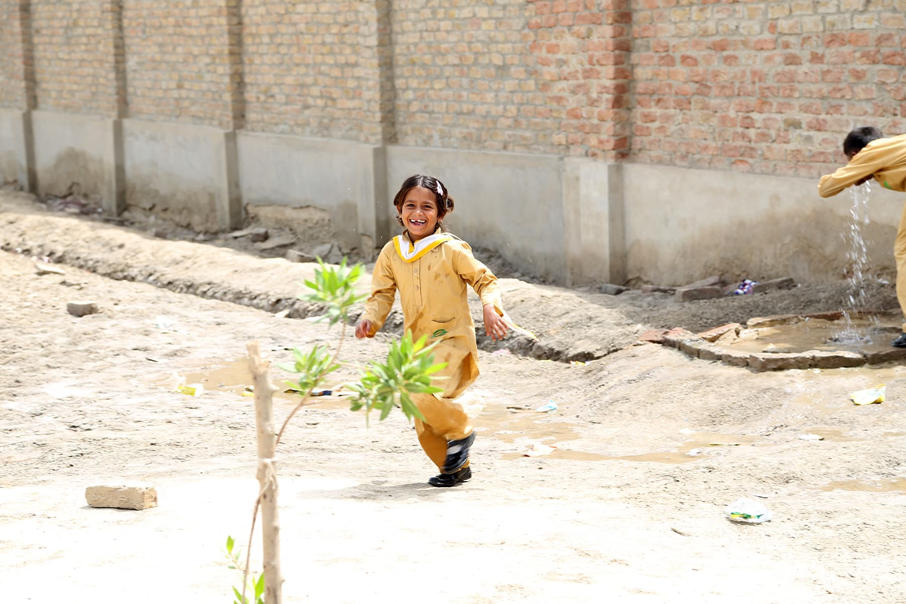 A young student smiles for the camera, she plays in the school ground during recess. - Photo by Mustafa Ilyas
