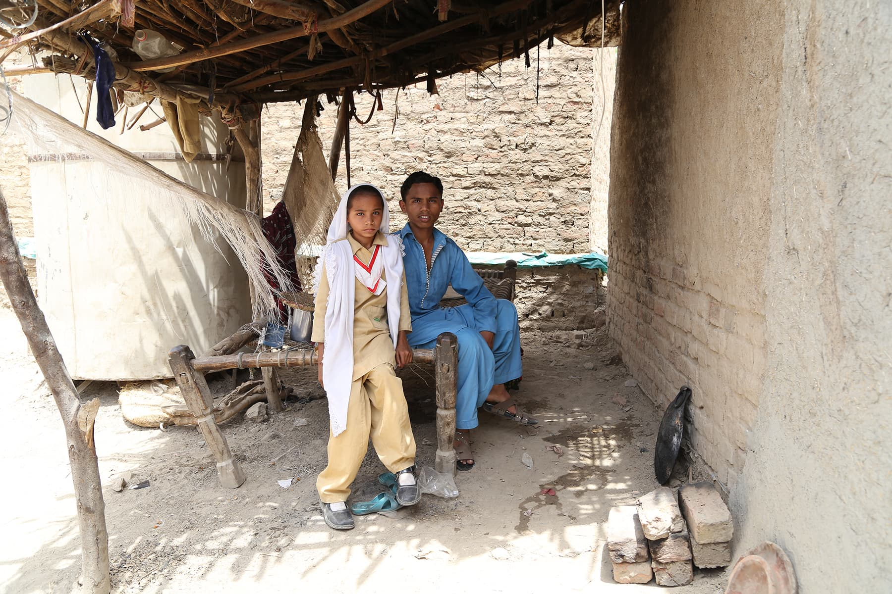 Khalil Ahmed pictured with his sister at his home in Gambat. - Photo by Mustafa Ilyas