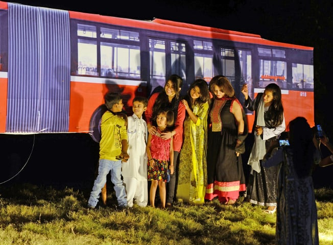 Families pose for a photograph next to a cut out of a metro bus in Islamabad on Wednesday. — Dawn