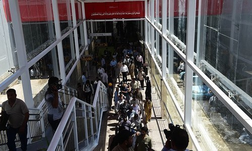 Media representatives and workers gather at the Metro Bus station in preparation of the inauguration in Islamabad. —AFP