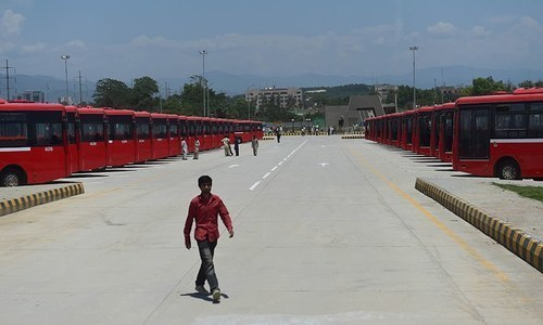 A worker walks at the Metro Bus station in Islamabad. —AFP