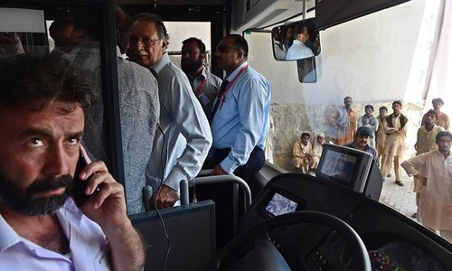 Minister for Information and Broadcasting Pervaiz Rashid (C) boards a Metro Bus along with media representatives in Islamabad. —AFP