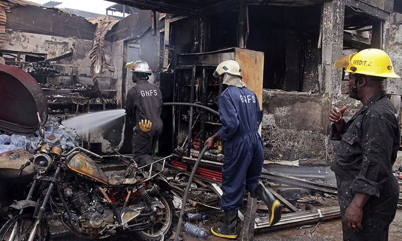 Firefighters spray water over the smoldering remains a gas station following an explosion in Accra, Ghana. -AP