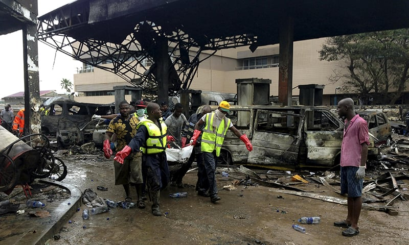 Rescue workers carry a corpse from the remains of a petrol station that exploded overnight killing around 90 people in Accra, Ghana. -Reuters