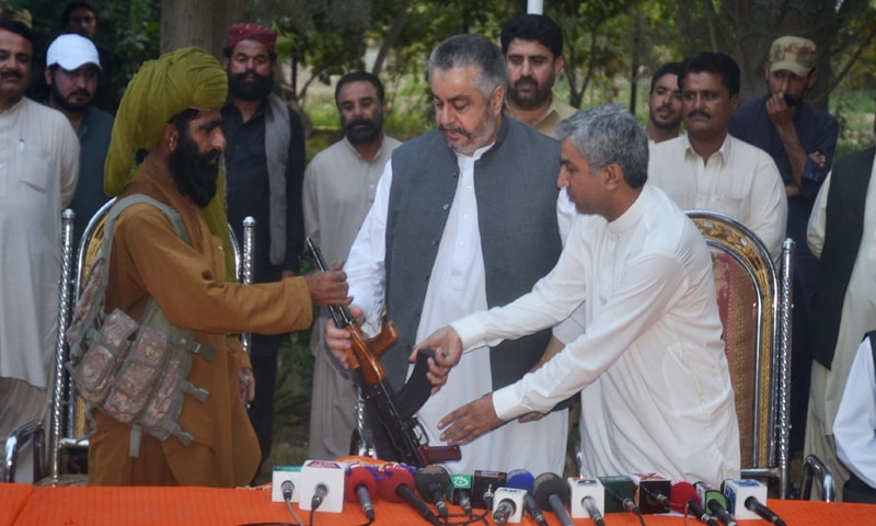 QUETTA: Wali Mohammad alias Haji Kalati, a leader of the banned United Baloch Army which is a splinter group of Harbiyar Marri-led Baloch Liberation Army, surrenders his arms at the residence of provincial Irrigation Minister Nawab Jangeez Khan Marri (second from right).—PPI