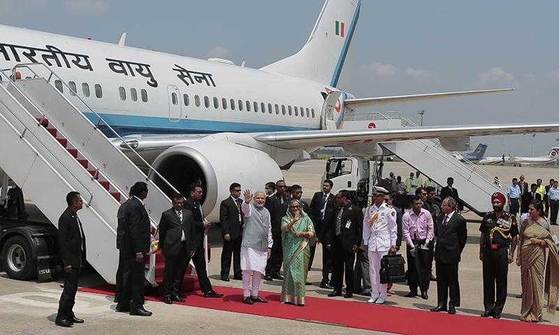 Indian Prime Minister Narendra Modi and Bangladesh's Prime Minister Sheikh Hasina wave to the media upon Modi's arrival at the Hazrat Shahjalal International airport in Dhaka, Bangladesh, Saturday, June 6, 2015. -AP