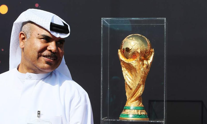 A Qatari official stands near the FIFA World Cup trophy following its arrival in Doha, on December 12, 2013 as part of trophy's world tour. — AFP/File