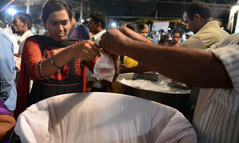 An Indian woman collects live fish prior to receiving fish medicine from members of the Bathini Goud family at the exhibition grounds in Hyderabad