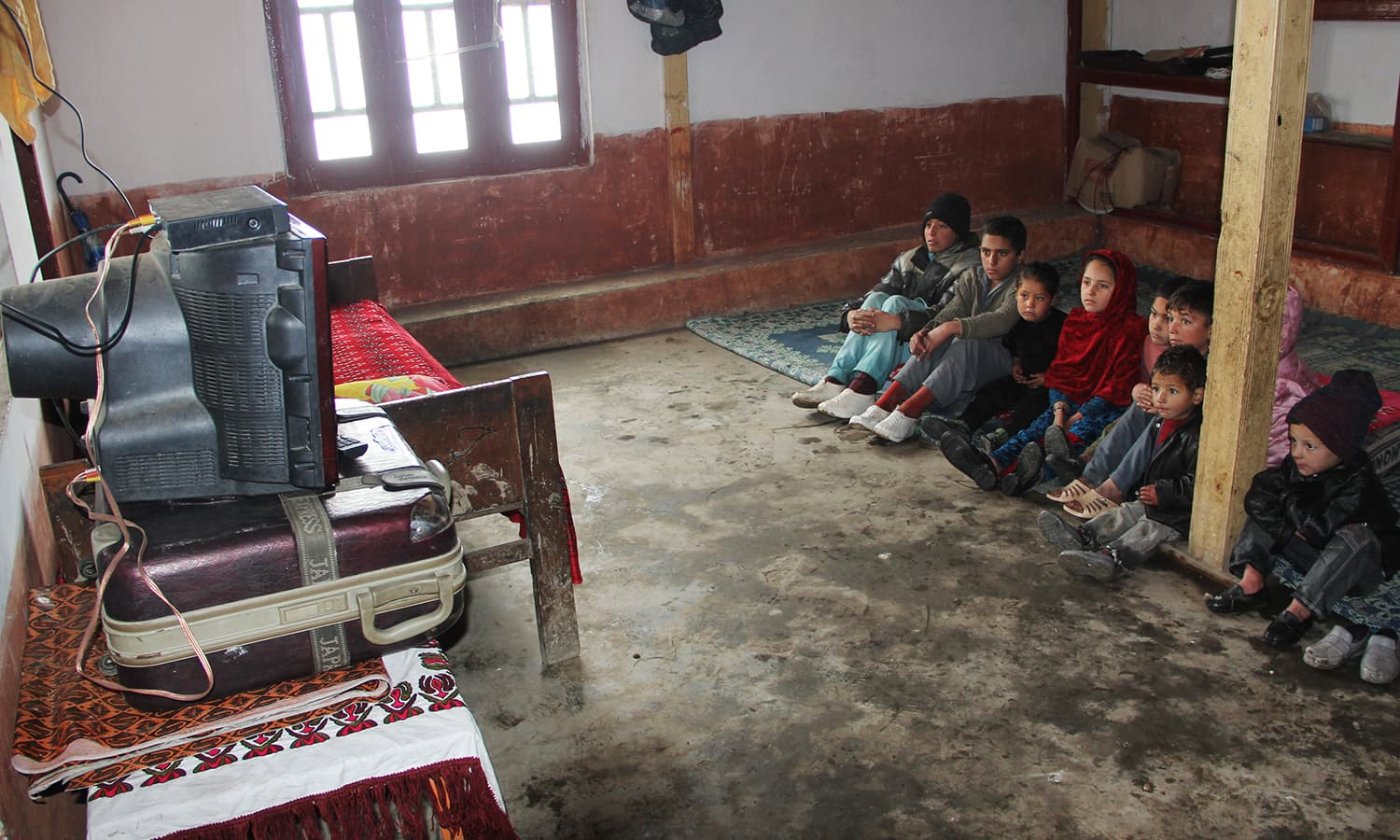 Local kids in Swat watching TV at their home.
