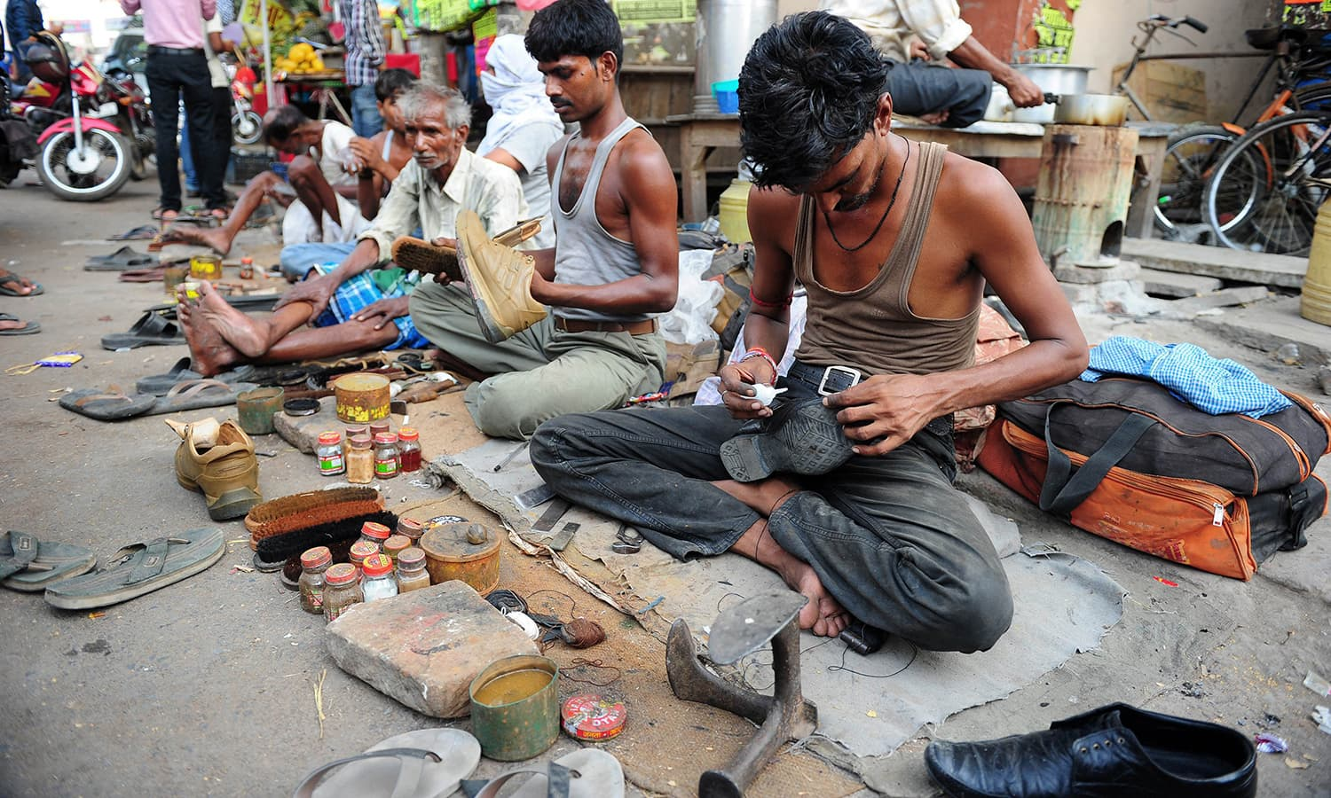 An Indian cobbler repairs a shoe at road-side in Allahabad. -AFP
