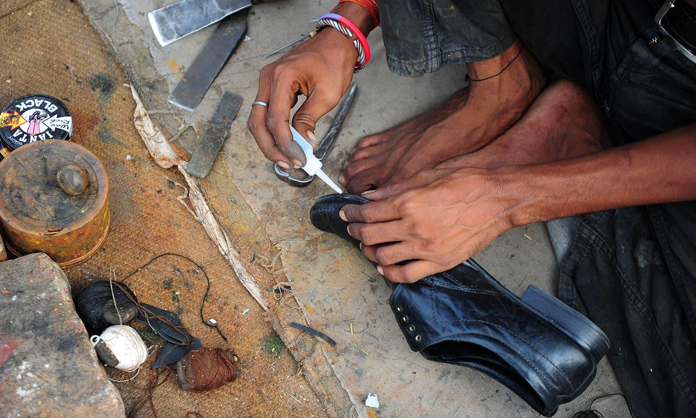 Repairing an an officer's shoe.-AFP