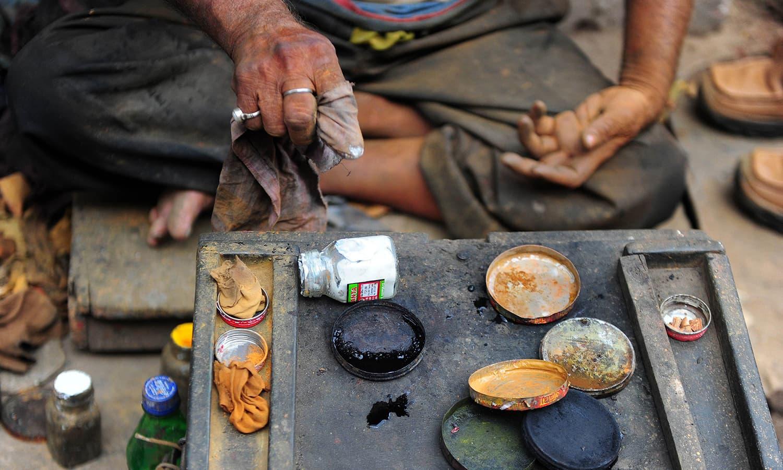 A cobbler prepares coloured shoe-polish.-AFP