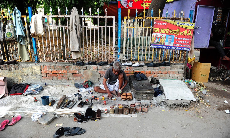 Indian cobbler working at the road-side.-AFP