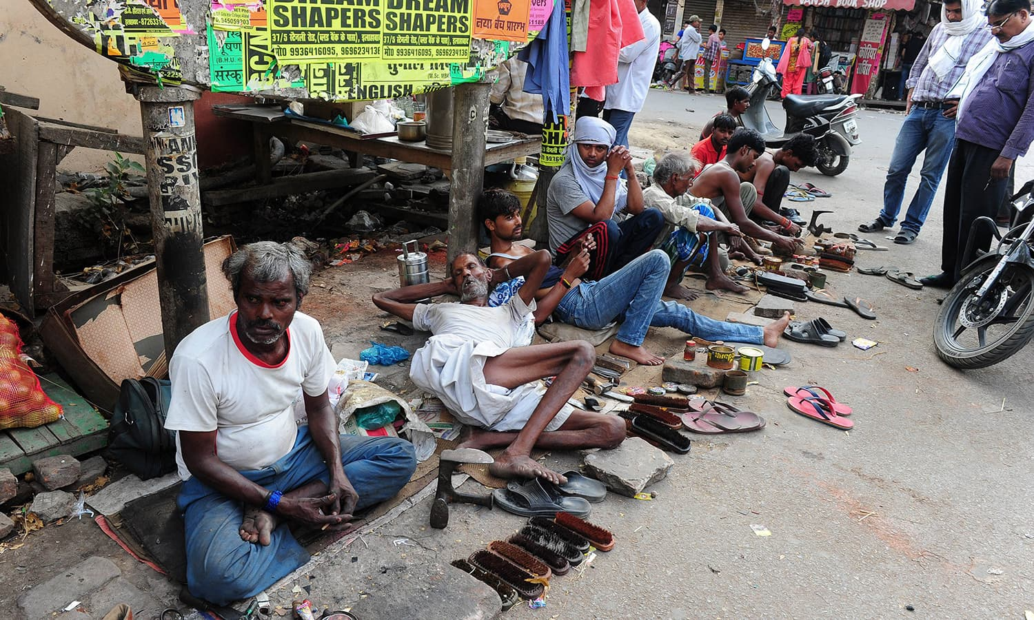 Cobblers wait until they get their delegated shoes for the day, on the way of repair. -AFP