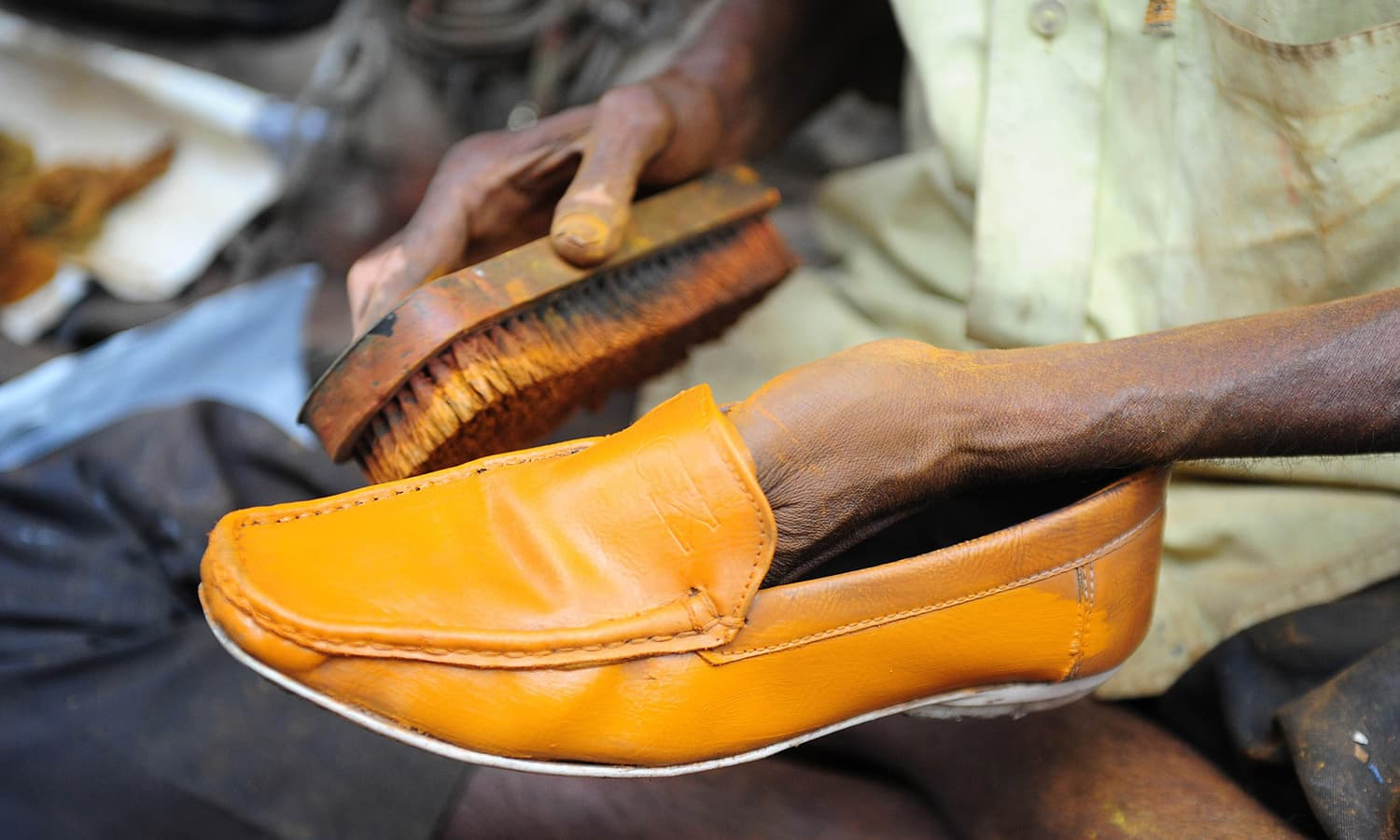 Polishing a shoe at the road-side. -AFP