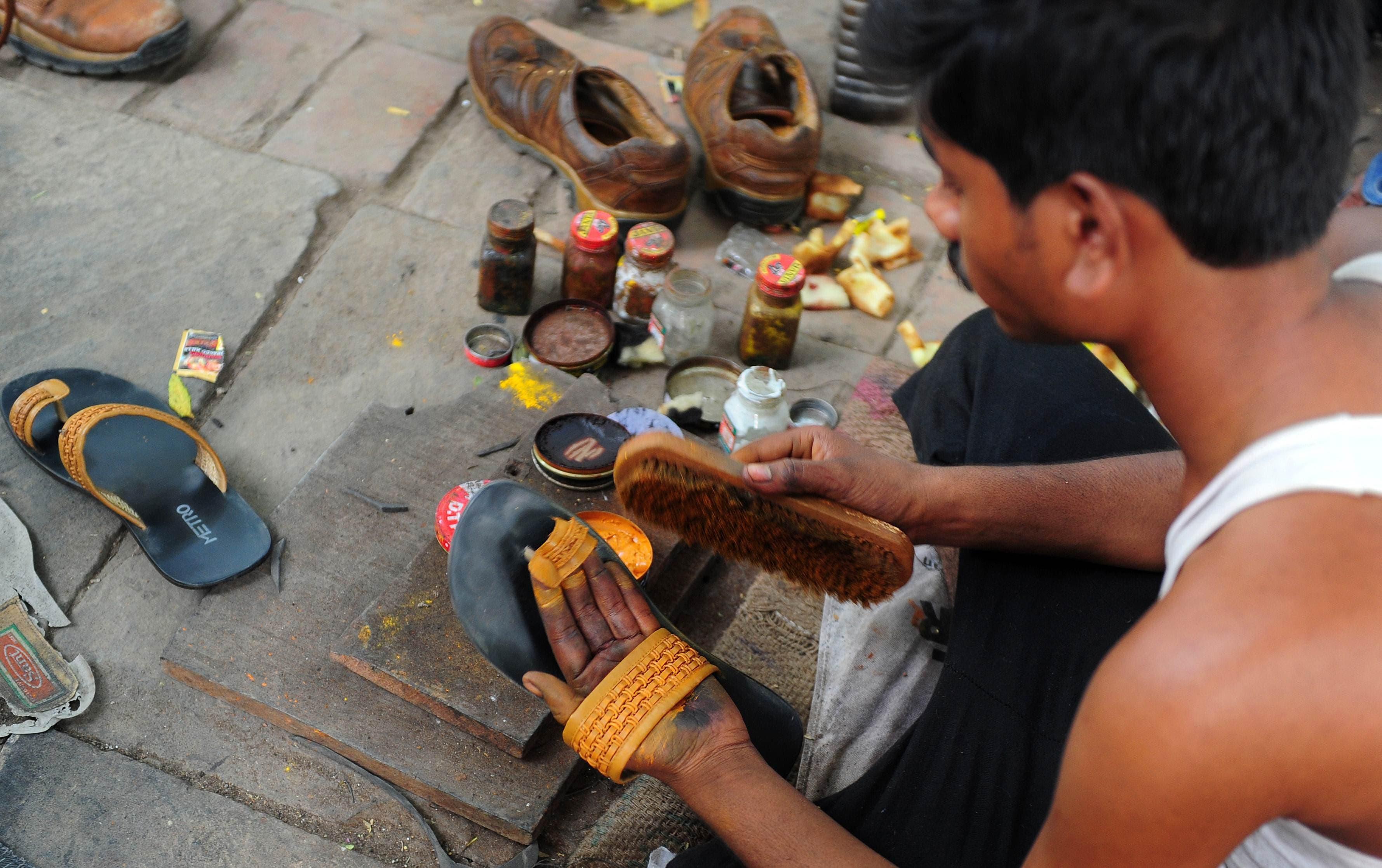 A cobbler artfully paints the sandal yellow. -AFP