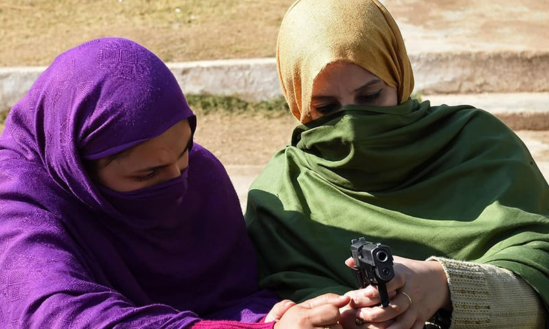 Teachers handle a pistol during a weapons training session for school, college and university teachers at a police training centre in Peshawar on January 27, 2015. —AFP