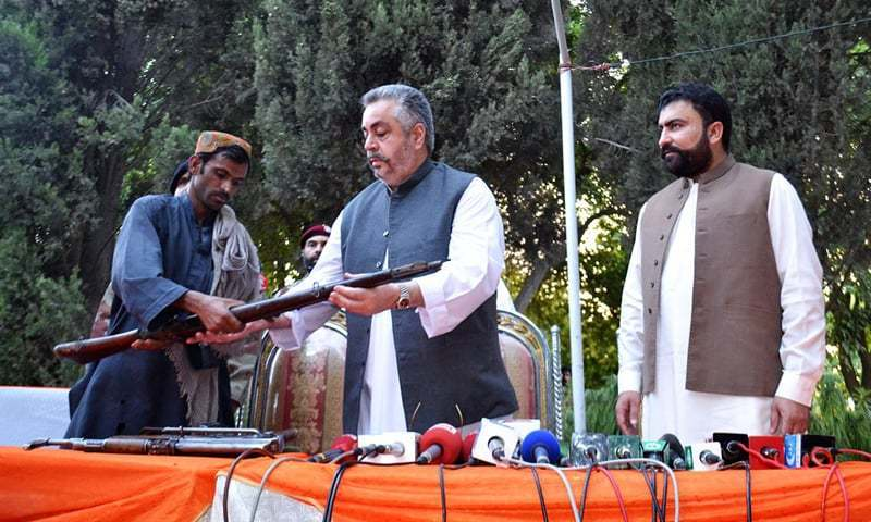 A man belonging to a banned militant group surrenders his arms to Balochistan Irrigation Minister Nawab Jangayz Marri during a press conference Saturday.- Online/File