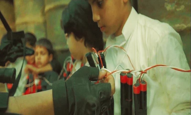 A soldier attempts to defuse explosives strapped to children. ─ ISPR