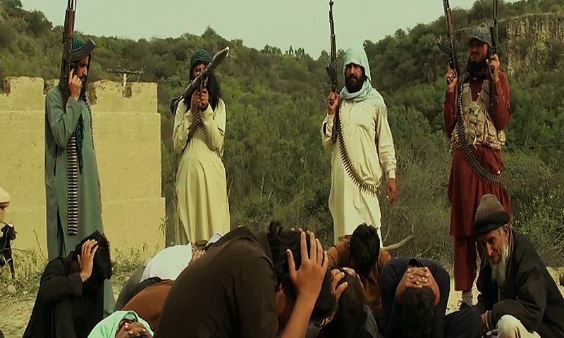 Actors posing as militants stand guard over cowering residents. ─ ISPR