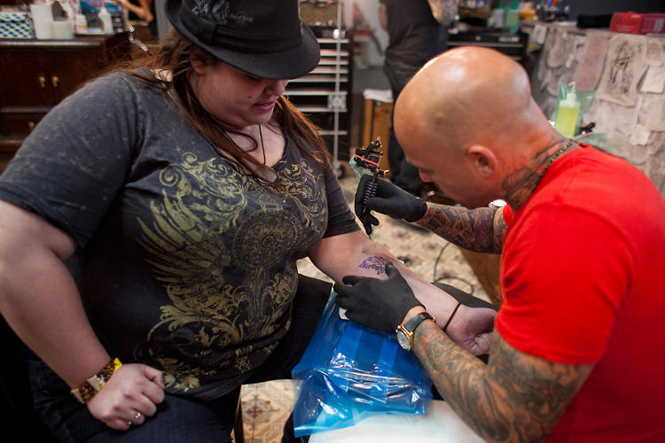 Tattoo artist Ami James works on a fan. Photograph: Fast Company Cocreate