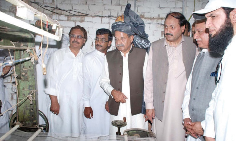 KP Governor Sardar Mahtab Ahmad Khan inspects a power loom after reopening an industrial unit in Bara, Khyber Agency, on Wednesday. — Dawn