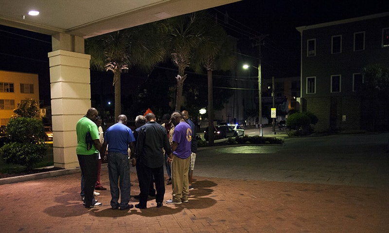 A small prayer circle forms nearby where police are responding to a shooting at the Emanuel AME Church in Charleston, South Carolina. —Reuters