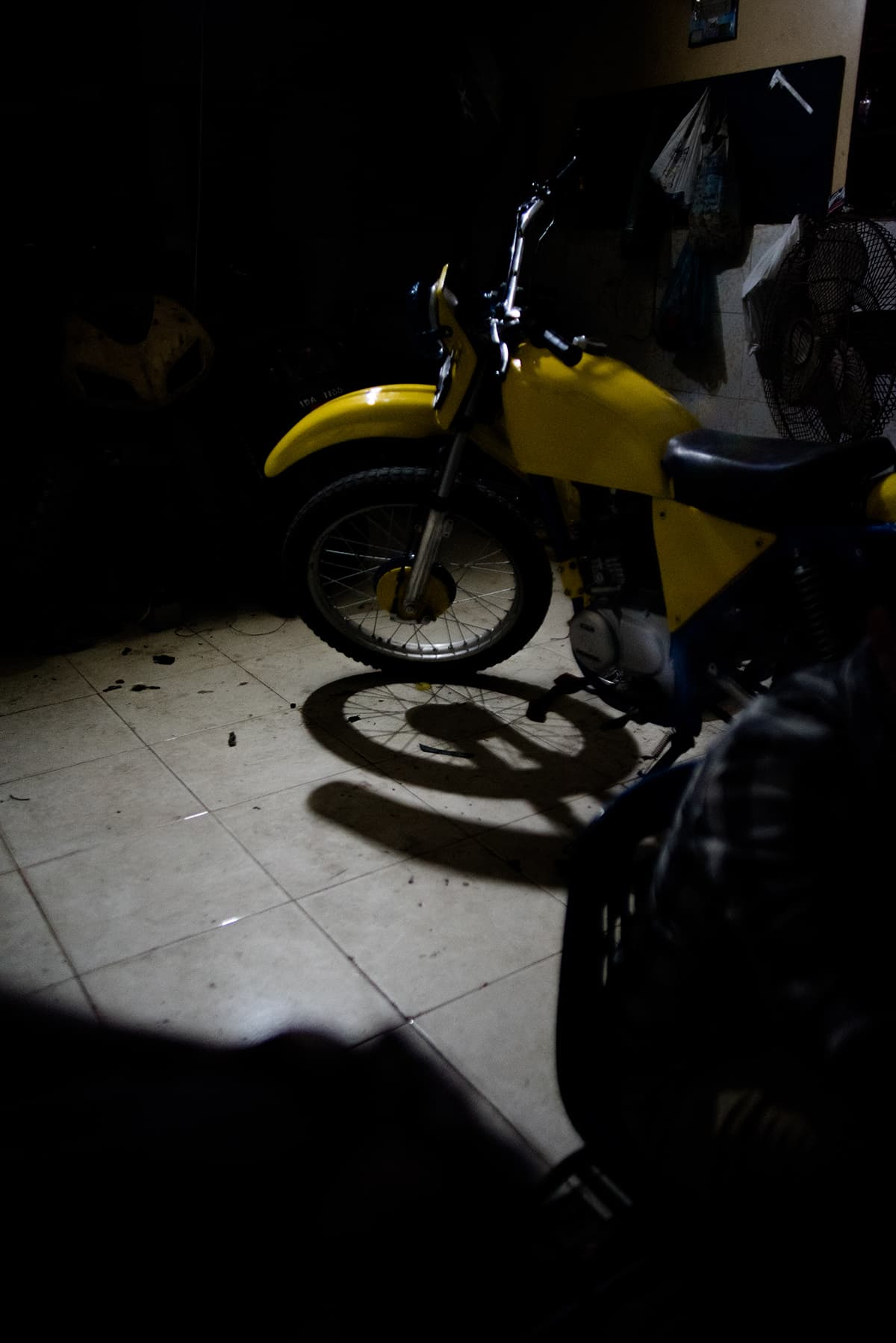 A newly painted motorcycle stands at a workshop, ready for racing
