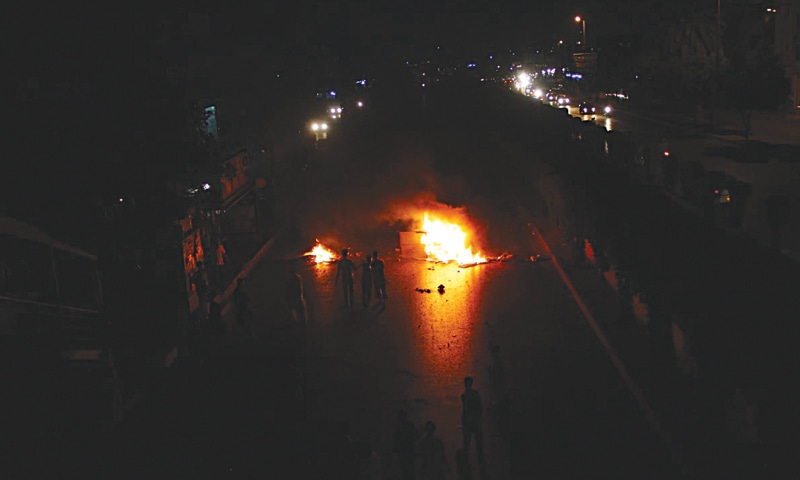 Residents of North Nazimabad area burn tyres and furniture on the road during a demonstration against power breakdown and prolonged loadshedding.—Online