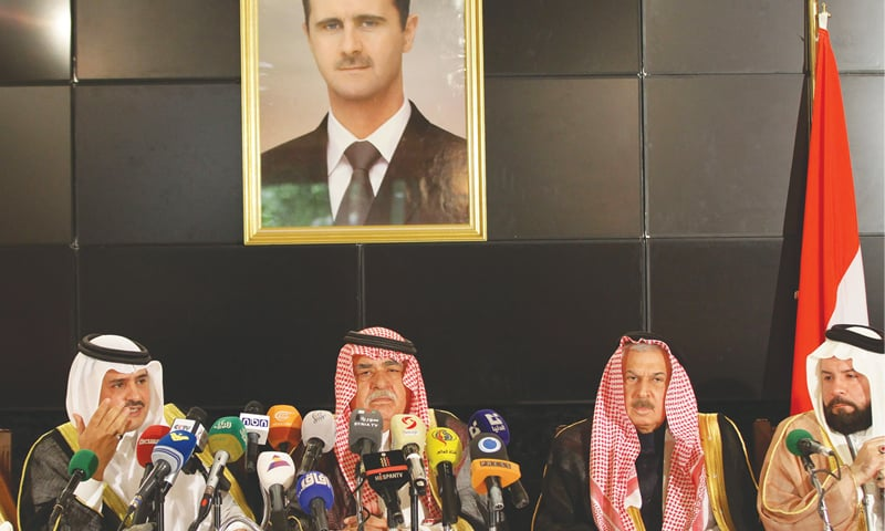 DAMASCUS: Sheikh Mohammed Faris (second from left) of the Tay tribe sits under a portrait of Syrian President Bashar al-Assad as he addresses a press conference of tribal leaders on Friday.—AFP