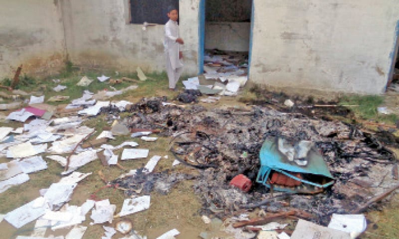 A boy stands inside a Pesco office burnt by protesters in Swabi on Friday. — Dawn