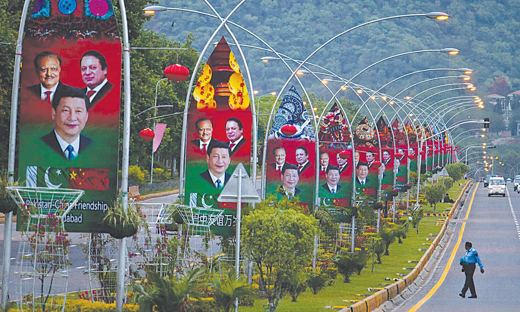 A police officer walks past billboards showing pictures of Chinese President Jinping Xi with President Mamnoon Hussain and Prime Minister Nawaz Sharif put up to welcome the former on his visit to Islamabad in April.—AP
