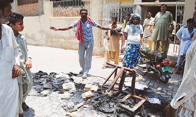 People gather outside the Hesco office after consumers protesting against prolonged loadshedding hours and frequent outages ransacked it and torched electricity meters and furniture on Friday.—Online