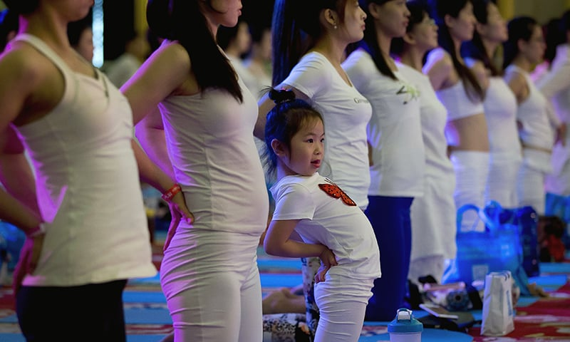 A child performs yoga at a hotel banquet hall to mark the International Yoga Day, in China. ─ AP