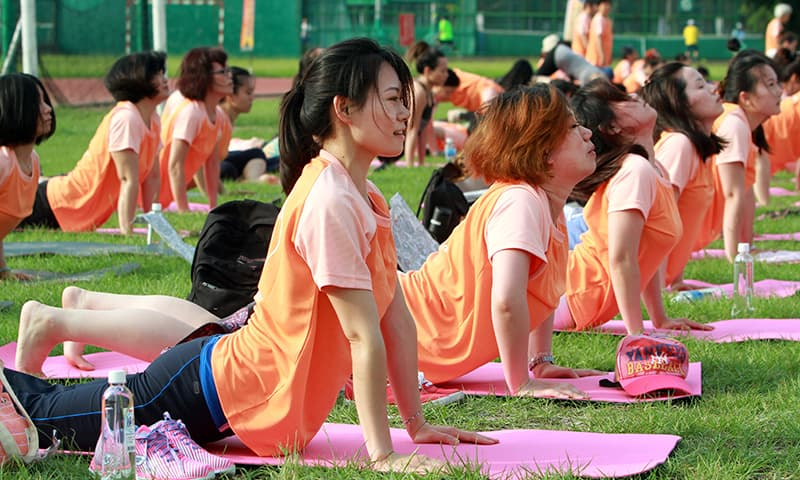 Taiwanese perform yoga poses at the start of International Yoga Day in Taipei, Taiwan. ─ AP