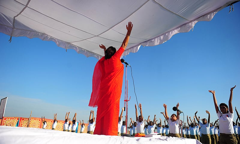 An Indian yoga teacher leads National Cadet Corps (NCC) members as they perform yoga on the banks of the river Ganga in the Jhusi area, at Kriyayoga Ashram in Allahabad. on June 21, 2015. ─ AFP