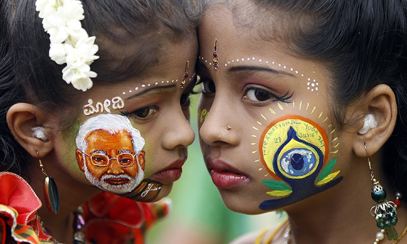An Indian girl, left, displays a picture of Indian Prime Minister Narendra Modi painted on her face as another sports the logo of International Yoga Day in Bangalore, India. ─ AP