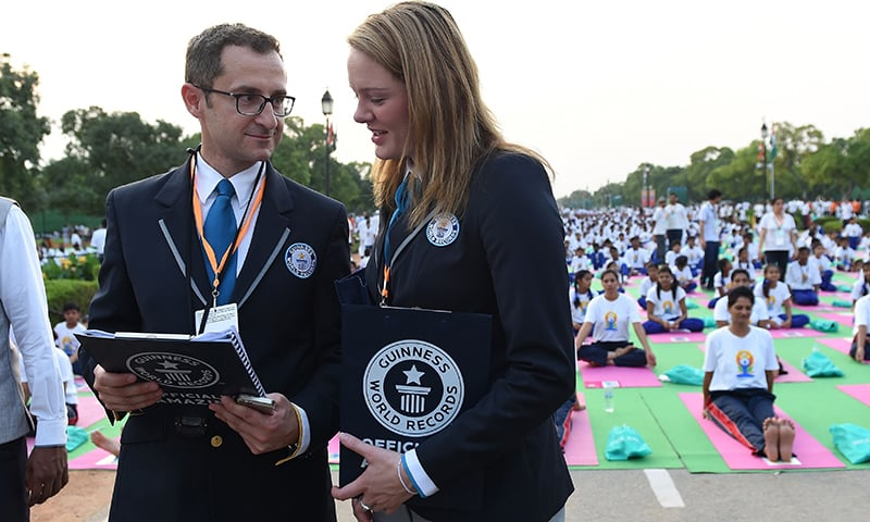Guinness World Recocrds Representatives Marco Frigatti (L) and Victoris Julie Tweedy talk to each other as Indian yoga practitioners prepare to take part in a mass yoga session to mark the International Yoga Day in New Delhi. ─ AFP