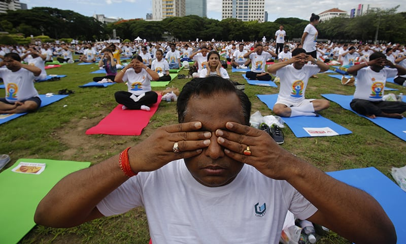 Thousands of people participate in a yoga exercise in Thailand. ─ AP